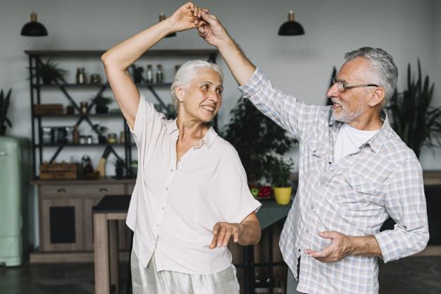 couple de seniors dansant dans son salon